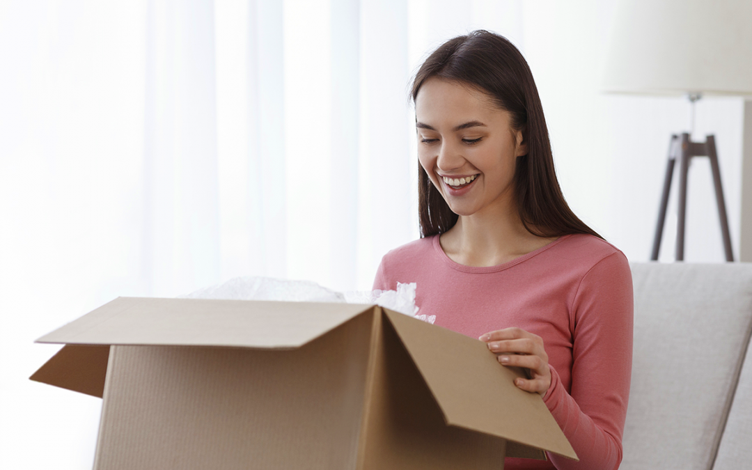 Young woman smiling and opening a box full of treats