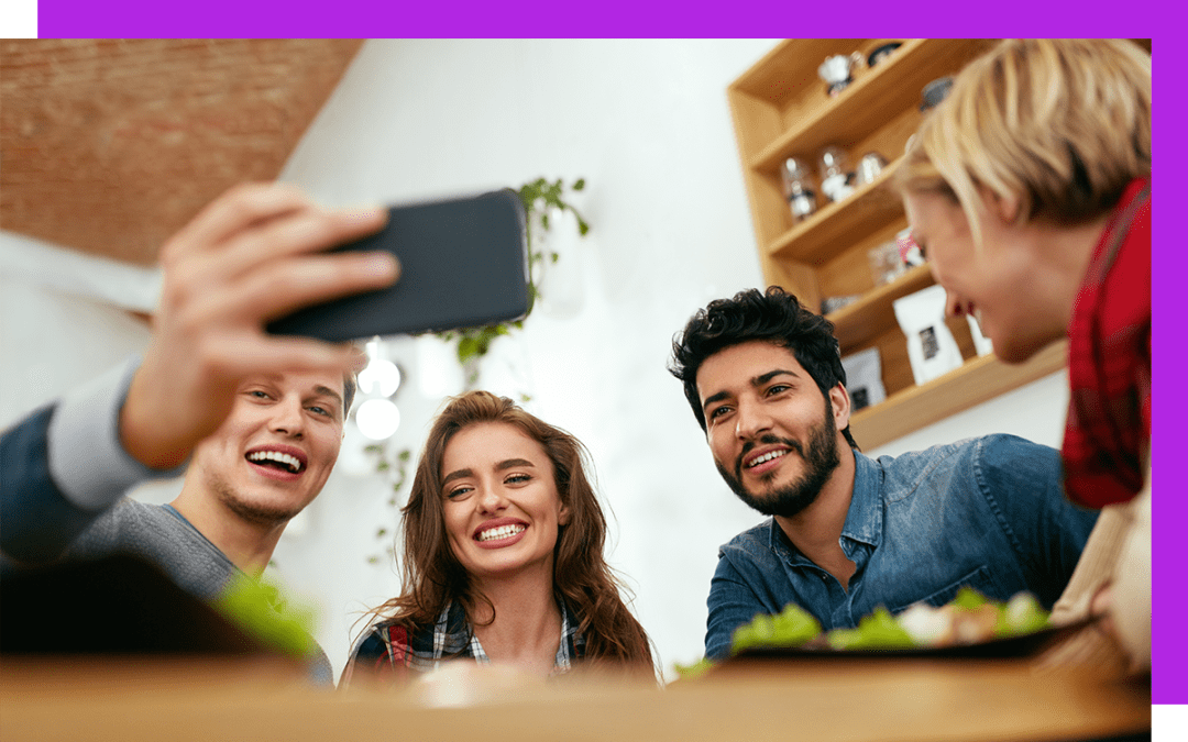 four employees taking a selfie with one smart phone and smiling in a workspace