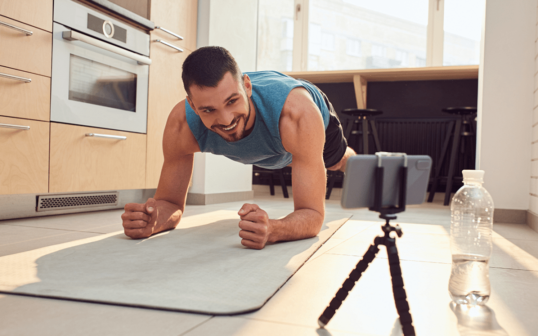 male holding a plank in living room over a virtual fitness session