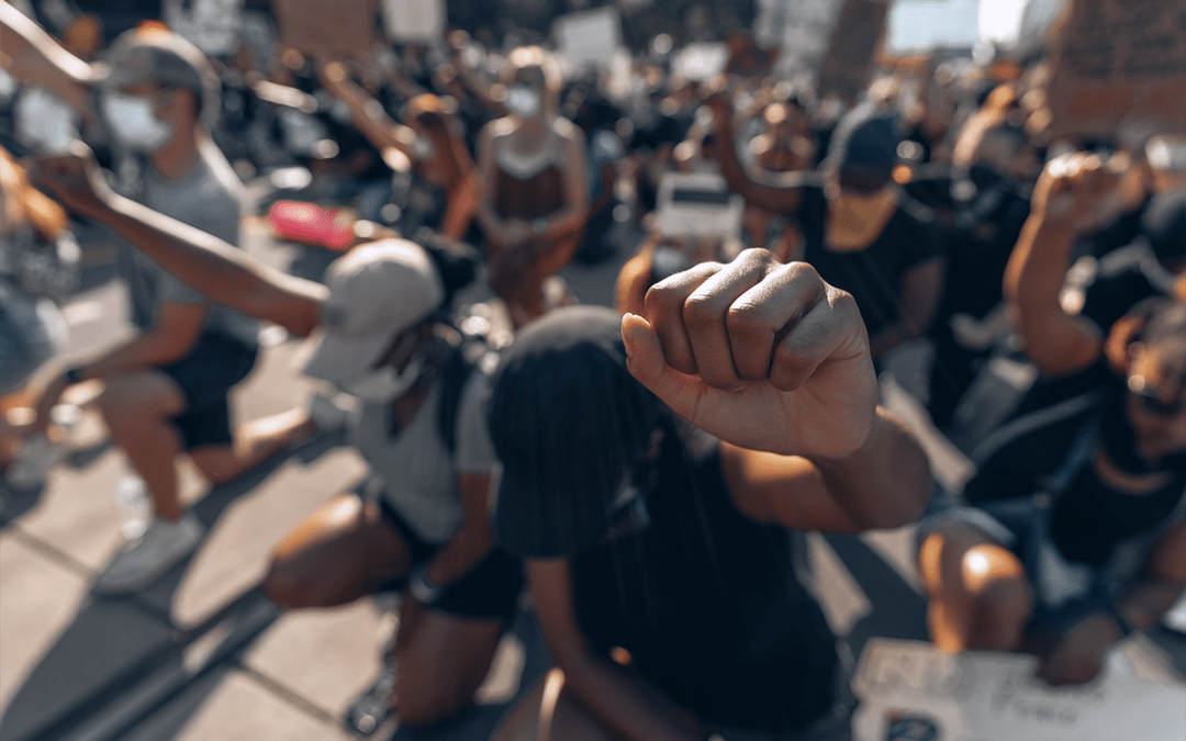 people standing with their fists high in a black lives matter march